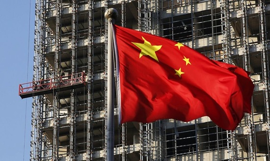 File photo of a Chinese national flag fluttering at a construction site for a new residence complex in Beijing