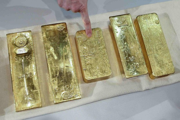 An-employee-of-Deutsche-Bundesbank-points-at-a-gold-bar-during-a-news-conference