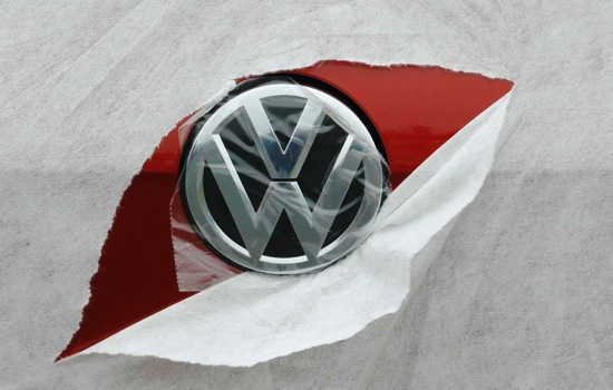 A VW badge is seen through torn wrapping as a Volkswagen Golf is delivered to a car dealership in Portslade near Brighton