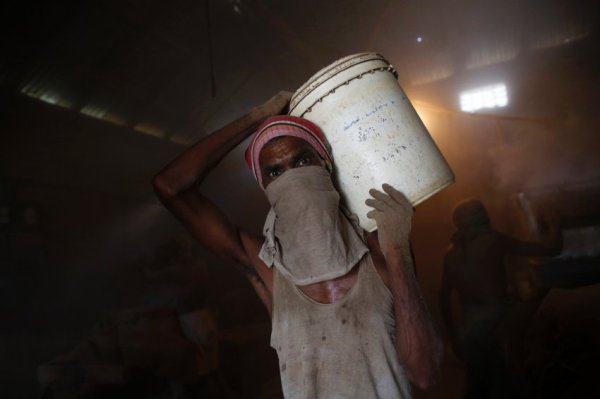 A worker carries a bucket while he works in a small bidi (cigarette) factory at Haragach in Rangpur district