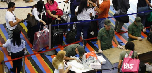 Soldiers checks the luggage of passengers at a security checkpoint at Simon Bolivar airport in La Guaira outside Caracas