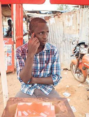 Abdulai Barrie, a 22-year-old agent for telecoms firm Africell, sits at his stall at Lumley Junction in Sierra Leone's capital Freetown