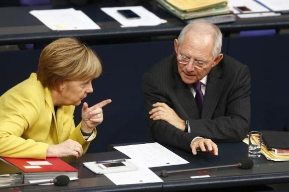 German Chancellor Merkel talks with Finance Minister Schaeuble prior to vote on the federal budget at Bundestag in Berlin