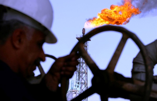 An Iraqi worker opens a pipe at Sheaiba oil refinery in Basra in this March 29, 2007 file photo. World markets braced for more volatility on December 17, 2014 as tumbling oil prices and a brewing financial crisis in Russia sent investors stampeding for safe havens such as the yen and U.S. Treasuries.   REUTERS/Atef Hassan/Files (IRAQ - Tags: ENERGY BUSINESS ENVIRONMENT)