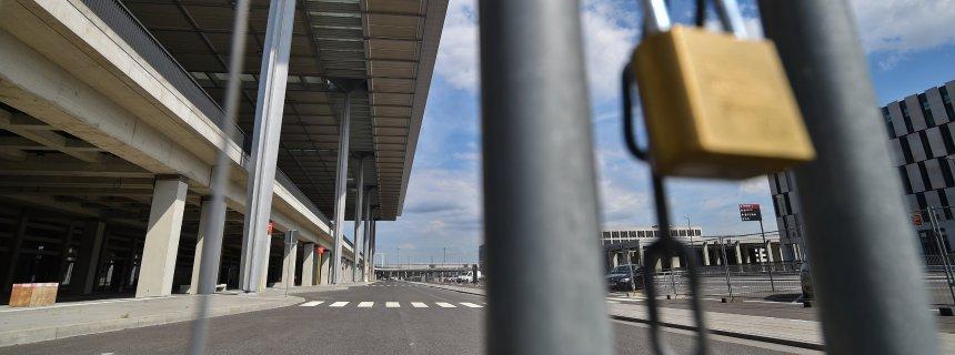 Ein Vorhängeschloss sichert einen Bauzaun am 16.06.2014 vor dem Terminal des Flughafens Berlin Brandenburg Willy Brandt (BER) in Schönefeld (Brandenburg). Mit den Korruptionsvorwürfen am neuen Hauptstadtflughafen beschäftigt sich am gleichen Tag der Flughafen-Ausschuss des Potsdamer Landtags. Zu der Sitzung will auch Flughafenchef Mehdorn erscheinen, der eine Taskforce zur Ermittlung von möglichen Korruptionsfällen am Flughafen BER eingesetzt hat. Foto: Patrick Pleul/dpa +++(c) dpa - Bildfunk+++