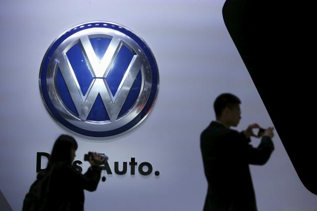 Guests stand next to a Volkswagen logo at the stage of the company at the 16th Shanghai International Automobile Industry Exhibition in Shanghai, April 20, 2015. REUTERS/Aly Song