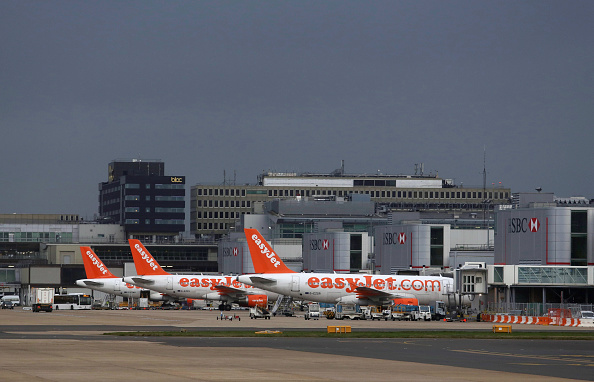 Three Airbus Group NV aircraft, operated by EasyJet Plc, stand at HSBC Holdings Plc branded departure gates at London Gatwick airport in Crawley, U.K., on Wednesday, Dec. 3, 2014. Britain said it will scrap the Air Passenger Duty departure tax for children under 12 from May 1 and plans to extend the move to all under-16s, lifting shares of EasyJet Plc, Flybe Group Plc and British Airways owner IAG SA. Photographer: Chris Ratcliffe/Bloomberg via Getty Images