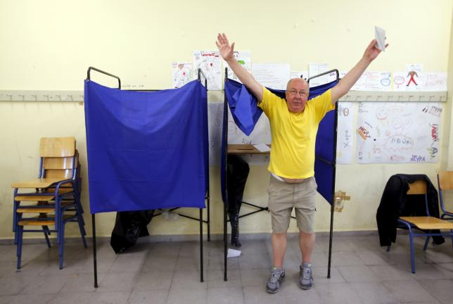A man raises his arms as he leaves a polling booth before casting his ballot during a referendum vote in Athens, Greece, July 5, 2015. REUTERS/Jean-Paul Pelissier