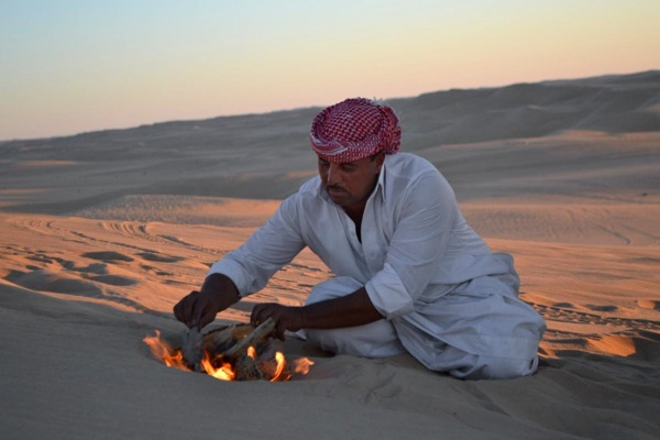 FILE - This September 2012 file photo shows desert safari driver Ahmed Bakrin building a small fire to make mint tea before sunset during a trek through the Great Sand Sea outside the Egyptian oasis of Siwa, roughly 450 miles (about 725 kilometers) southwest of Cairo. At least 12 people were killed and 10 injured in Egypt's southwestern desert Sunday, Sept 13, 2015, when security forces mistakenly fired on a group of Mexican tourists, Egyptian officials said. The Mexican Foreign Ministry confirmed the incident and said at least two of the dead were Mexican nationals. (AP Photo/Kim Gamel, File)