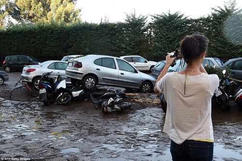2D10FDAF00000578-3259269-Destructive_power_A_woman_inspects_damaged_cars_and_bikes_in_Man-a-73_1443955238491