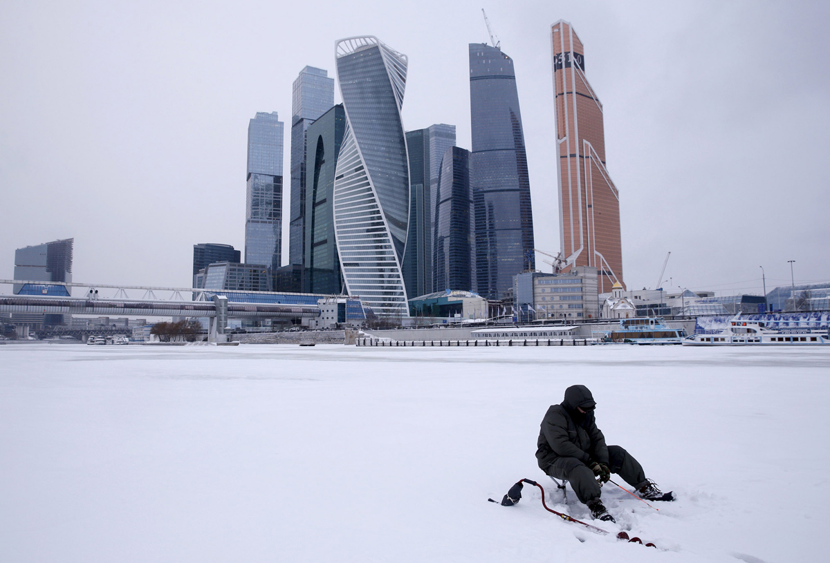 """A man fishes on the ice-covered Moskva river near the Moscow International Business Center also known as """"Moskva-City"""" in the capital Moscow, Russia, January 13, 2016. REUTERS/Maxim Zmeyev - RTX227AM"""