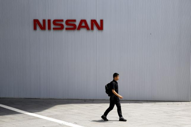 A man walks past the logo of Nissan Motor Co. at the company's showroom in Yokohama, south of Tokyo June 23, 2015.  REUTERS/Toru Hanai