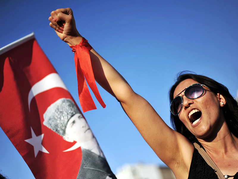 """A protester raises her fist and shouts a slogan during a demonstration on June 9, 2013 on Gundogdu square in Izmir. Turkey's defiant Prime Minister Recep Tayyip Erdogan on June 9 told supporters his patience """"has a limit"""" as he went on the offensive against mass protests to his Islamic-rooted government's decade-long rule. As tens of thousands of protesters massed in Istanbul, the capital Ankara and the western city of Izmir, in unrest now in its 10th day, Erdogan staged his own rallies across three cities to fire up loyalists of his ruling Justice and Development Party (AKP). AFP PHOTO /OZAN KOSEOZAN KOSE/AFP/Getty Images"""