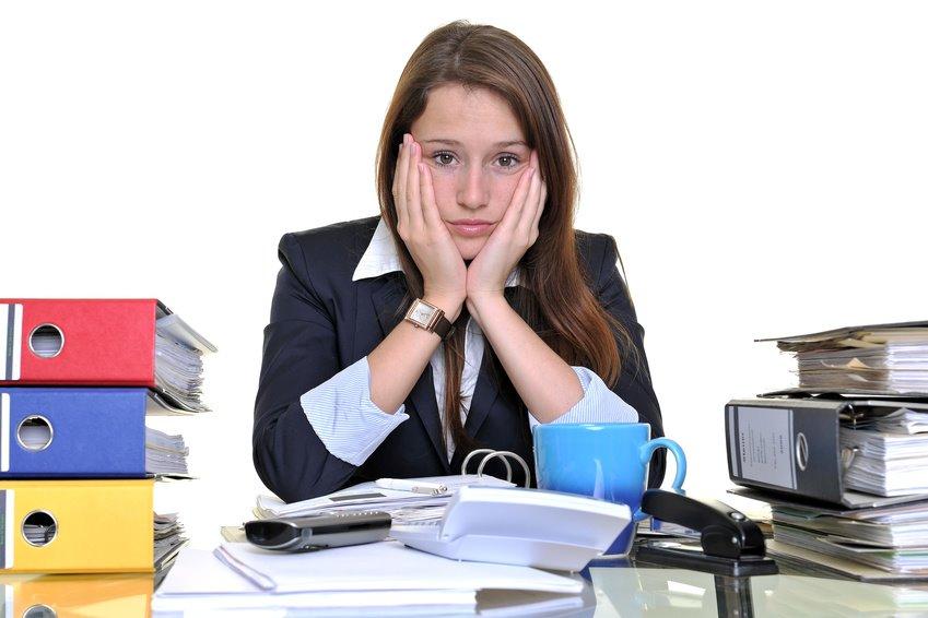 Junge Frau arbeitet im Büro zwischen Akten